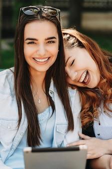 Due adorabili fidanzate divertendosi seduti su una panchina guardando la telecamera ridendo con in mano una tavoletta.