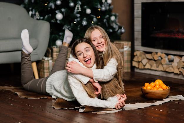 Due belle ragazze in posa con baciare l'espressione del viso alla festa di compleanno. signora europea dai capelli lunghi in piedi accanto ad albero e regali
