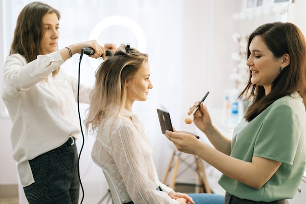 Due truccatori applicano i capelli e il trucco alla sposa nel camerino