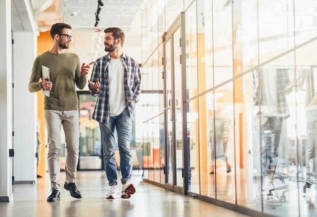 Due colleghi maschi discutono di qualcosa mentre vanno al lavoro