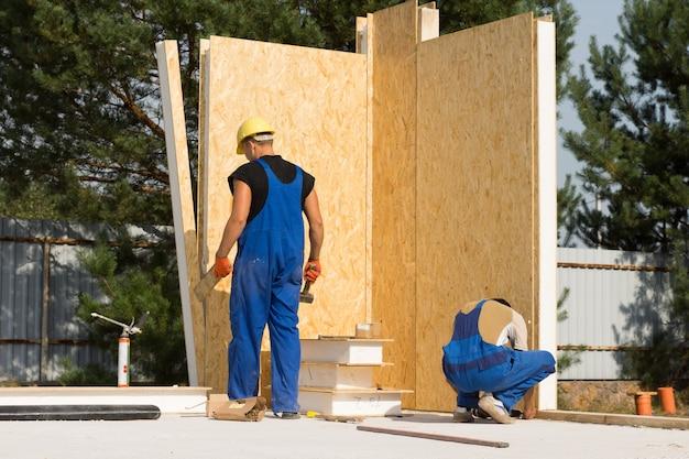 Due operai edili maschi impegnati nella costruzione di una casa immobiliare