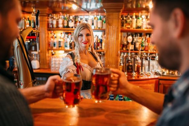 Due amici maschi che tintinnano tazze di birra nel pub, cameriera al bancone