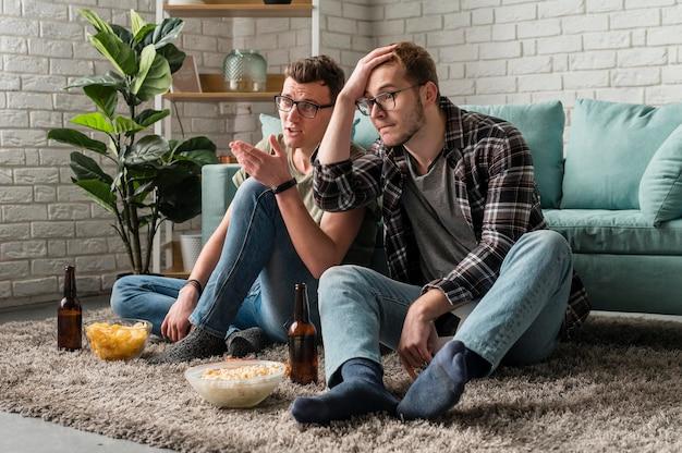 Due amici maschi che guardano insieme lo sport in tv mentre bevono birra e spuntini