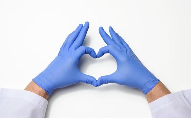 Due mani maschili in guanti medicali sterili in lattice blu mostra un gesto del cuore su uno sfondo bianco, il concetto di bontà, aiuto e volontariato