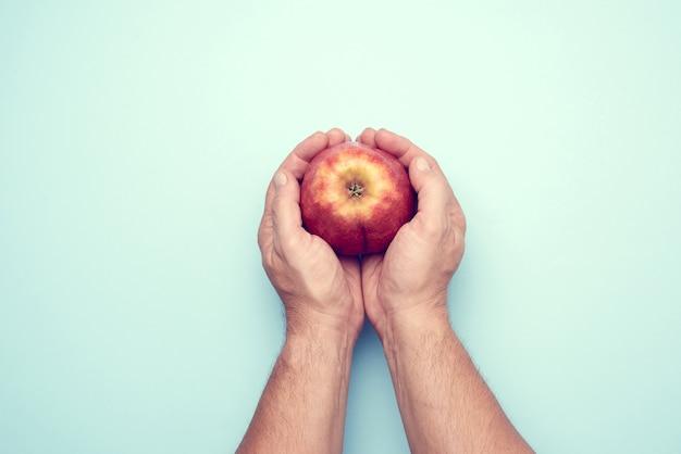 Due mani maschii tengono una mela rossa matura, vista dall'alto