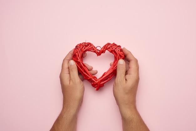 Due mani maschii che tengono un cuore di vimini rosso, concetto di amore