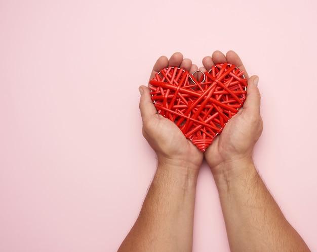 Due mani maschii che tengono un cuore di vimini rosso su una rosa