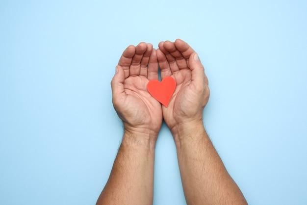 Due mani maschii che lottano cuore di carta rosso su un blu