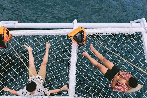 Due maschi si rilassano e si abbronzano sulla rete del catamarano mentre usano uno smartphone
