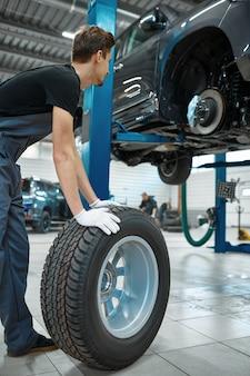 Due meccanici maschi riparano la ruota, servizio auto