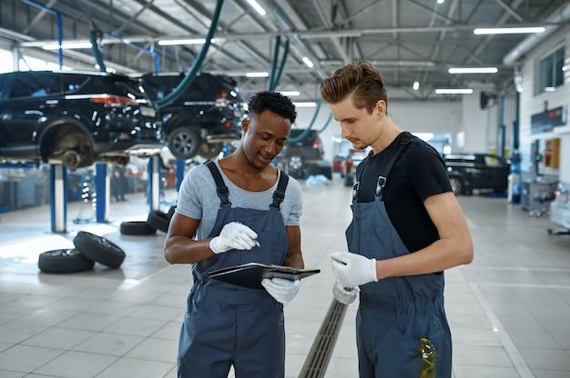 Due meccanici maschi che parlano al servizio auto