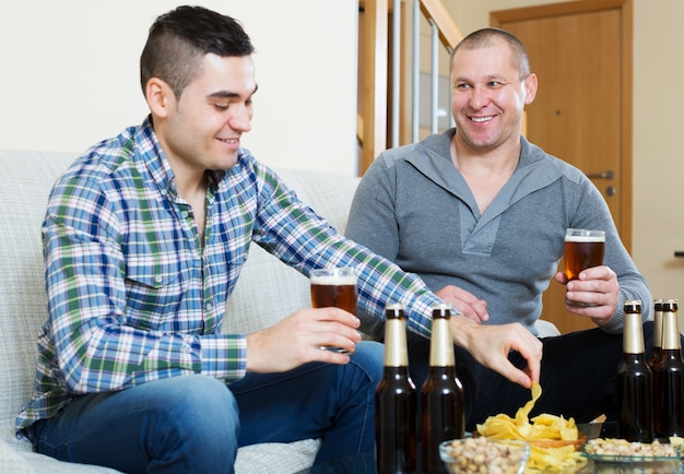 Due uomini con birra si siedono e parlano