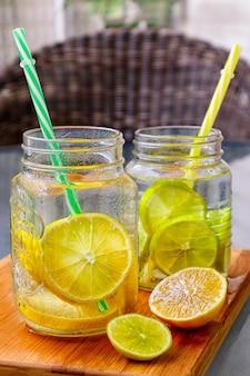 Due bicchieri di barattolo di vetro di limonata fatta in casa con parte di limoni su un tagliere di legno