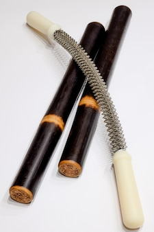 Due bastoncini per massaggi e attrezzature per massaggi su sfondo bianco