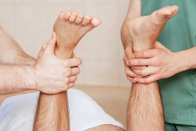 Due massaggiatori stanno massaggiando i piedi dell'uomo.