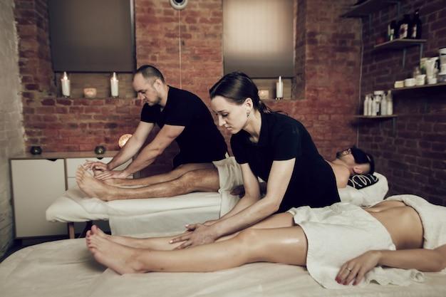 Due massaggiatori che fanno un massaggio ai piedi a una giovane coppia. uomo e donna che gode di un massaggio in un salone della stazione termale. concetto di trattamenti termali.