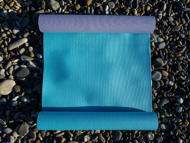 Due materassini per yoga, pilates o fitness giacciono sugli scogli in riva al mare.