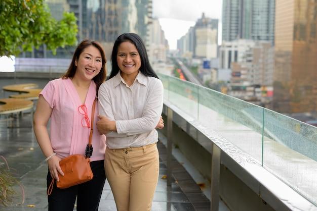 Due donne asiatiche mature insieme contro la vista della città