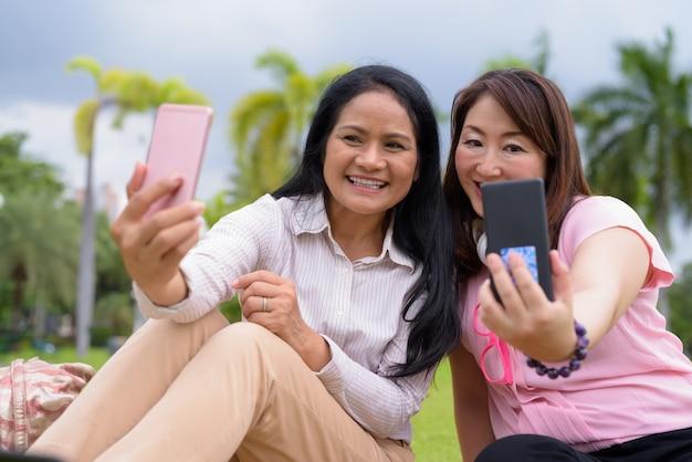Due donne asiatiche mature che si rilassano insieme al parco