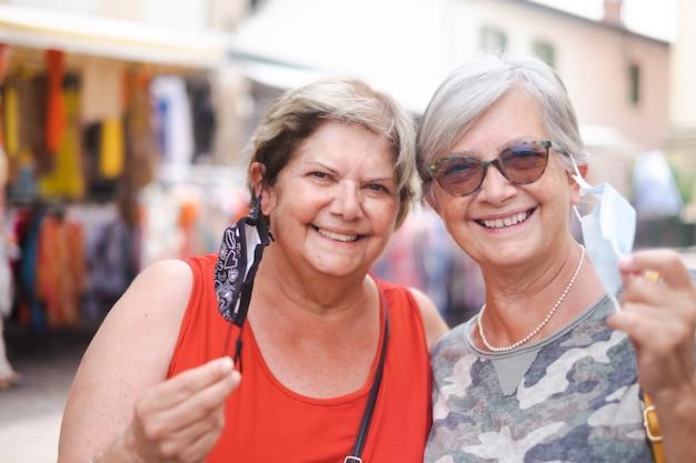 Due donne mature con un'espressione felice, si tolgono le maschere chirurgiche in posa per il ritratto di famiglia. persone, emozioni e amicizia