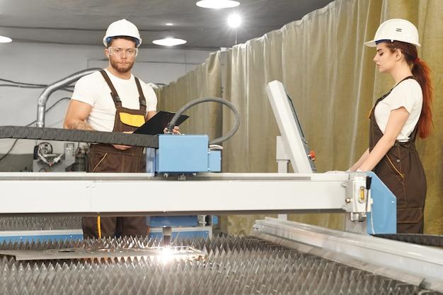Due meccanici che controllano il processo di taglio al plasma