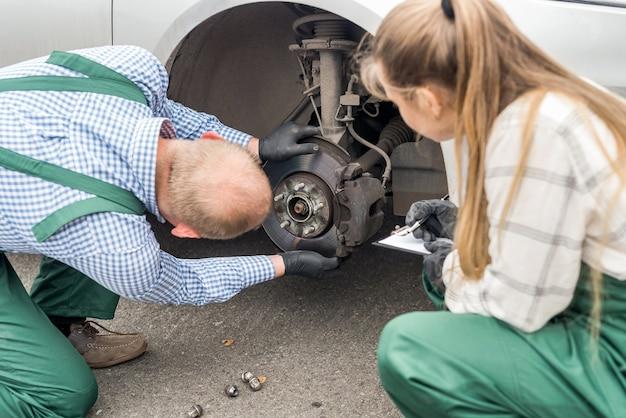 Due meccanici che esaminano il disco del freno in auto