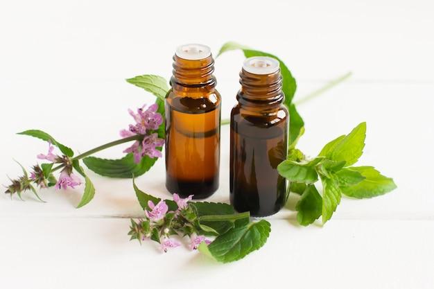 Due bottiglie mediche di contagocce e spie fresche di menta piperita con fiori su sfondo bianco. angolo ravvicinato. il concetto di benessere.