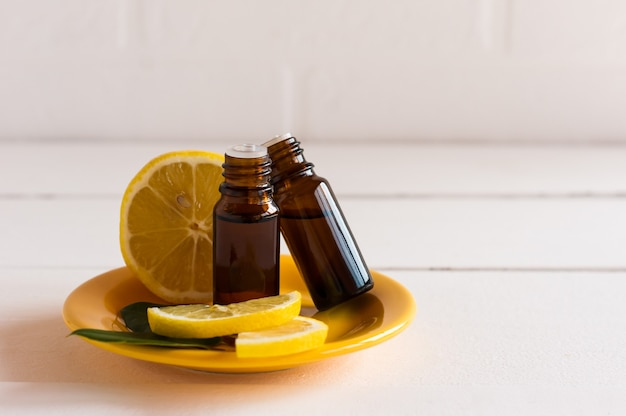 Due bottiglie mediche con una gocciolina con olio essenziale di agrumi su un tprel di ceramica gialla su uno sfondo di limone e un muro di mattoni bianchi.