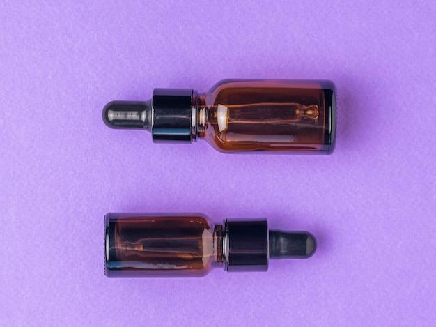 Due bottiglie mediche con una pipetta su uno sfondo viola. disposizione piatta.