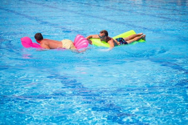 Due uomini fanno il bagno in piscina e si rilassano. foto di alta qualità