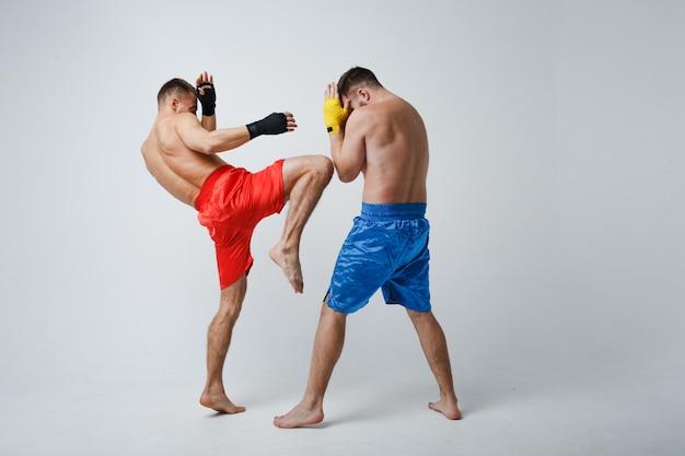 Due uomini pugili che combattono muay thai kickboxing sfondo bianco