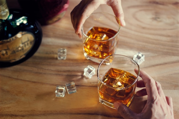 Due uomini tintinnano bicchieri di whisky