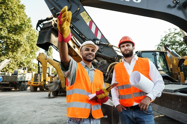 Due ingegneri discutono del loro lavoro in piedi contro le macchine edili