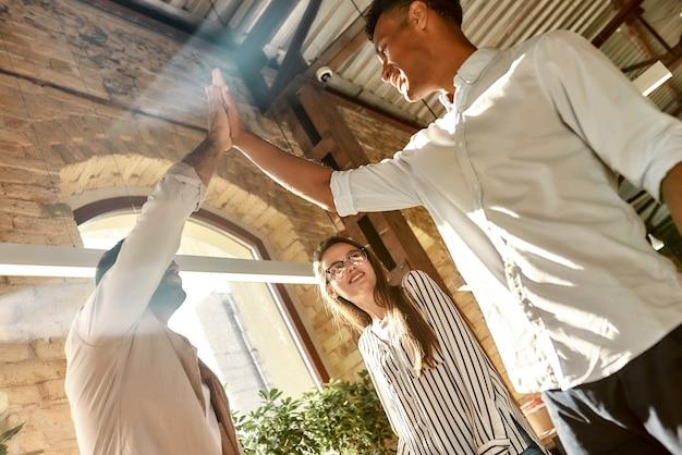 Due uomini che danno il cinque mentre sono in piedi con i colleghi nel lavoro di squadra dell'ufficio moderno