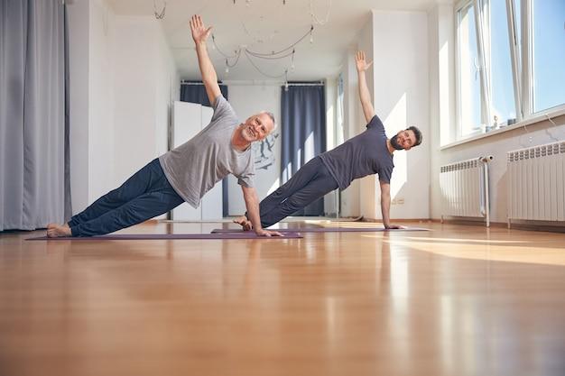 Due uomini che tengono una tavola laterale posano con le mani in alto alzate al soffitto