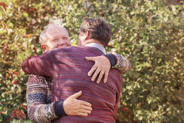 Due uomini che abbracciano nel parco di autunno