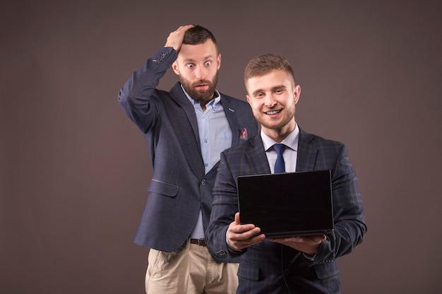 Due uomini che esaminano il computer portatile con sorpresa