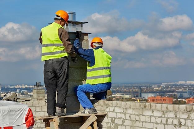Due uomini costruttori professionisti in abiti da lavoro e elmetti stanno installando un tubo per il sistema di ventilazione sul tetto dell'edificio in costruzione
