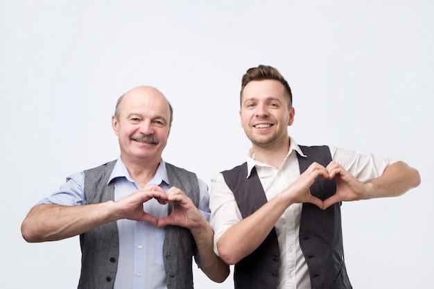 Due uomini mostrano il gesto del cuore