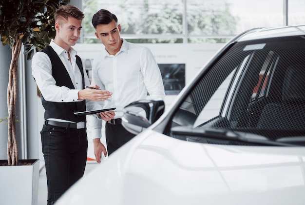Due uomini stanno nello showroom contro le auto. primo piano di un responsabile delle vendite in un abito che vende un'auto a un cliente. il venditore consegna la chiave al cliente.