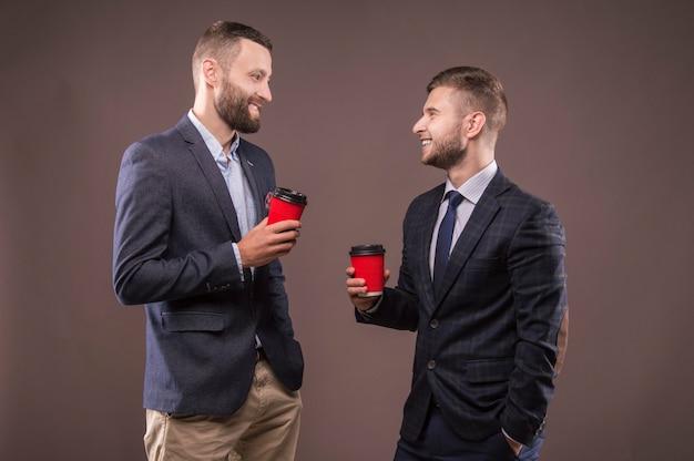 Due uomini in piedi con una tazza di caffè in mano sorridono e condannano l'argomento interessante