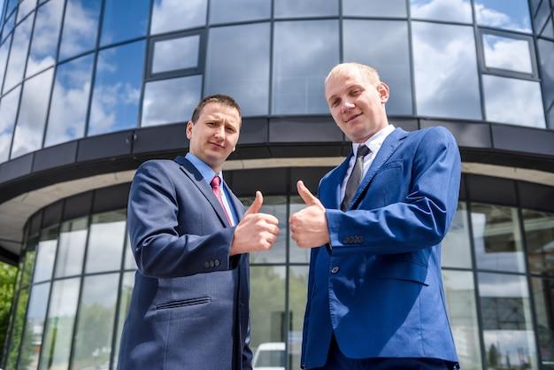 Due uomini in giacca e cravatta che mostrano i pollici in su all'aperto