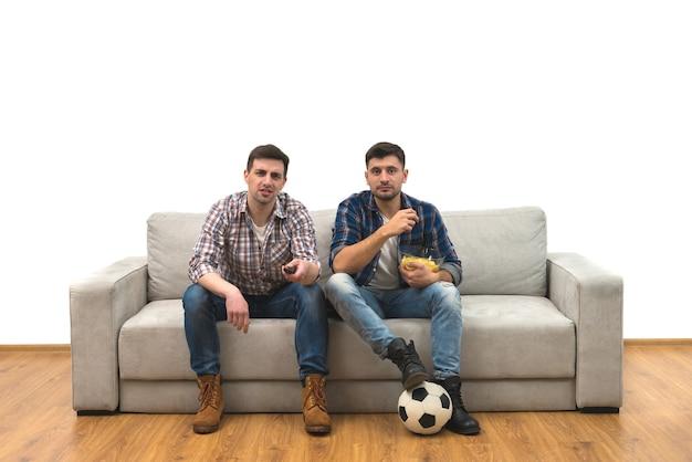 I due uomini guardano una partita di calcio sul divano sullo sfondo del muro bianco