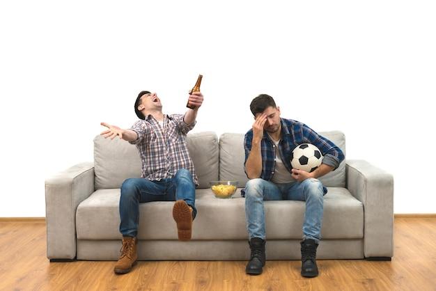 I due uomini con una birra e patatine guardano una partita di calcio sul divano