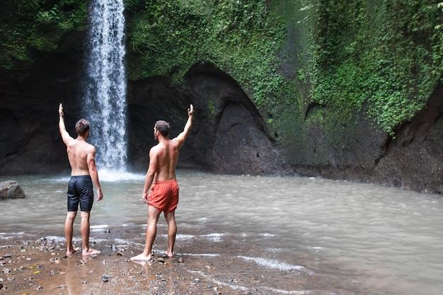 Due uomini con le mani in alto vicino alla bellissima cascata di tibumana a bali