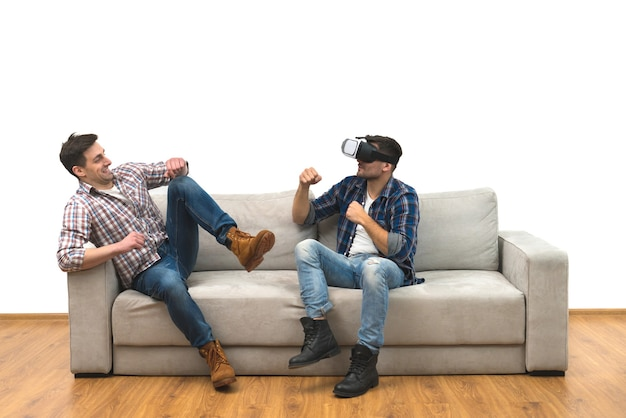 I due uomini con gli occhiali virtuali si divertono su un divano su uno sfondo di muro bianco