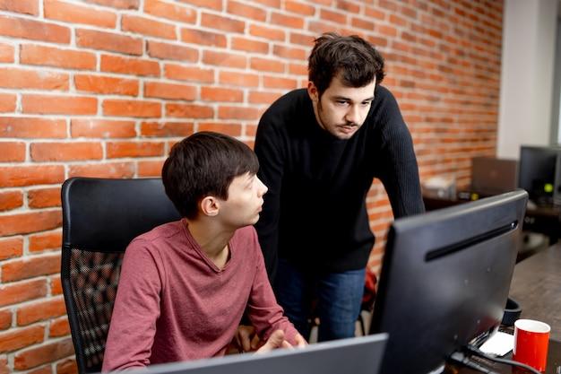 Due uomini che lavorano in un ufficio moderno. raggiungere i migliori risultati. due giovani fiduciosi stanno discutendo di piani aziendali