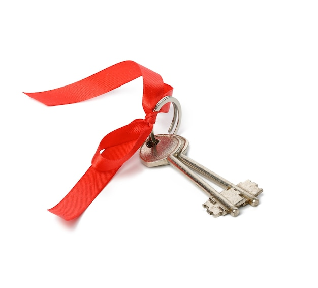 Due chiavi della porta di casa in metallo con nastro rosso isolato su sfondo bianco, concetto di acquisto di beni immobili