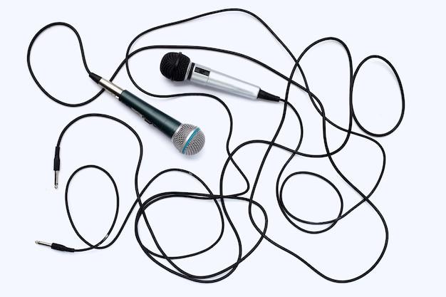 Due microfoni su sfondo bianco.
