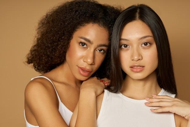 Due giovani donne di razza mista con una pelle perfetta che guardano la telecamera mentre posano insieme